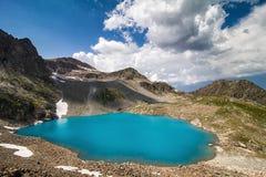Lac alpin parmi les roches Photographie stock libre de droits