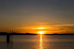 Lac au coucher du soleil, avec un pilier sur du ciel gauche et beau avec Photographie stock