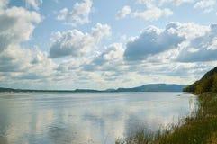 Lac avec l'opposé herbeux de rivage et de montagnes photos stock