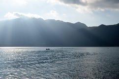 lac avec la lumière du soleil par des montagnes de fond Image libre de droits