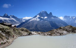 Lac Blanc on the background of the Alps. Lac Blanc on background snowy peaks of the Alps and cloudy blue sky, and the Lac Blanc chalet overlooking the lake Stock Photography