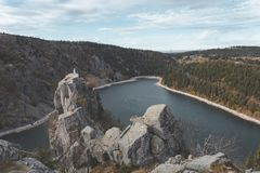 Lac Blanc from hiking trail through the vosges mountains in france. Beautiful bright blue mountain lake with statue on top of rock stock photography