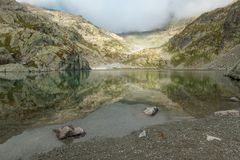 Lac blanc in muted tones of green, grey and beige. Under grey skies and mist, the calm waters of Lac Blanc - reached by hiking trails around Mont Blanc, France royalty free stock images
