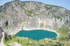 Lac bleu dans le cratère d'un volcan éteint en Croatie Photos stock