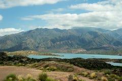 Lac bleu entouré par les collines vertes images stock