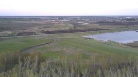 Lac bleu parmi des champs près de route large contre le village banque de vidéos