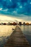 Lac Bokod sunset avec le pilier et pêcher les cottages en bois Images libres de droits