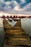 Lac Bokod sunset avec le pilier et pêcher les cottages en bois Image libre de droits