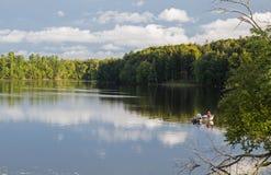 Lac calme avec le bateau de pêche Image stock