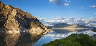 Lac calme dans l'ouest américain reflétant un point rocheux Images libres de droits
