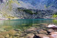Lac clair comme de l'eau de roche sur des montagnes de Retezat photos stock