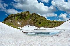 Lac congelé de montagne parmi les pentes rocheuses couvertes de neige Images libres de droits