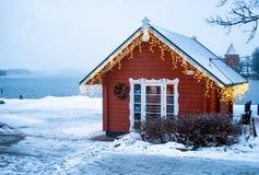 Lac congelé, neige et peu de maison en bois avec des lumières photos libres de droits