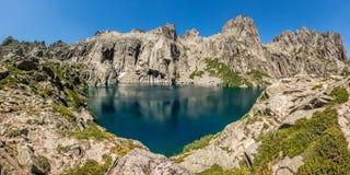 Lac de Capitello near Corte in Corsica. Dramatic rock formations surrounding the turquoise Lac de Capitello in the mountains above Restonica near Corte in Royalty Free Stock Images