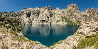 Lac de Capitello near Corte in Corsica. Dramatic rock formations surrounding the turquoise Lac de Capitello in the mountains above Restonica near Corte in Stock Photo