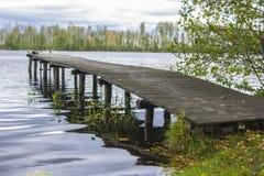 Lac de forêt de fond entouré par les arbres et la passerelle en bois Photo stock