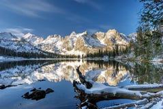 Lac de montagne d'hiver avec le rondin et les réflexions Photographie stock
