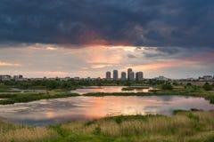 Lac de parc naturel dans le coucher du soleil avec quelques bâtiments images stock