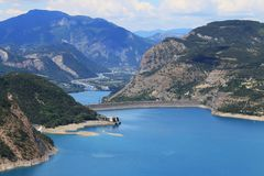 Dam in Lake Serre-Poncon and Durance river, Hautes-Alpes, France. Lac de Serre-Poncon is a lake in southeast France and one of the largest artificial lakes in royalty free stock photography