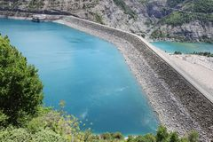 Dam and Power station of Lake Serre-Poncon, French Hautes-Alpes. Lac de Serre-Poncon is a lake in southeast France and one of the largest artificial lakes in stock photo