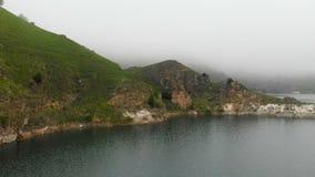 Lac de turquoise de montagne de vue aérienne parmi les collines en temps et brouillard nuageux de jour Paysages du Caucase du nor banque de vidéos