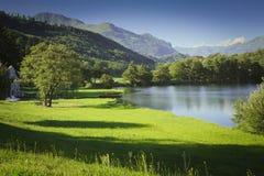 Lac en montagne avec le champ vert et le ciel bleu Photographie stock libre de droits