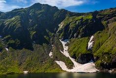Lac en montagnes avec la neige sur le flanc de coteau Photo stock