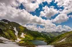 Lac en montagnes avec la neige sur le flanc de coteau Image stock