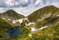 Lac en montagnes avec la neige sur le flanc de coteau Photos stock