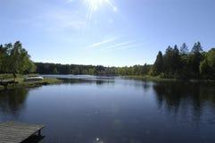 Lac ensoleillé avec le rampe de bateau images stock