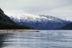 Lac entouré par les crêtes de montagne neigeuses Image stock