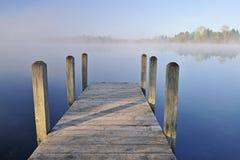 Lac et dock brumeux Photos stock