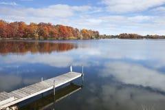 Lac et dock minnesota avec les arbres dans la pleine couleur d'automne, SK bleue Photographie stock libre de droits