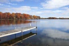 Lac et dock minnesota avec les arbres dans la pleine couleur d'automne, SK bleue Images stock
