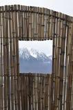 Lac et montagne avec la fenêtre en bambou Photographie stock libre de droits