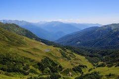 Lac et vallée alpine de prés avec la forêt en montagnes de Caucase Photo stock