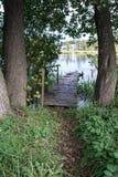 Lac karélien pendant le matin, l'herbe, les arbres et un pilier de bateau Images stock
