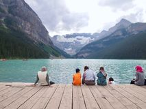 Lac Lousie - les gens s'asseyant sur l'eau avec le dos mountian photographie stock libre de droits