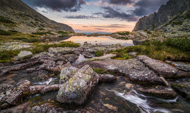 Lac mountain avec des roches dans le premier plan au coucher du soleil Photos libres de droits