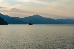 Lac mountain en brume de crépuscule avec le bateau démodé Photographie stock