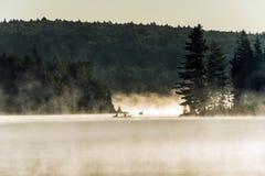 Lac ontario de Canada d'heure d'or de l'eau de deux de rivières canoës de canoë de brouillard brumeux de lever de soleil sur l'ea image libre de droits