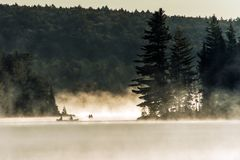 Lac ontario de Canada d'heure d'or de l'eau de deux de rivières canoës de canoë de brouillard brumeux de lever de soleil sur l'ea images libres de droits