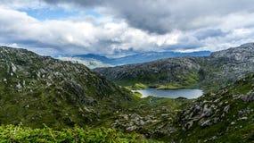 Lac parmi les collines rocheuses photographie stock