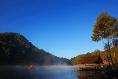 Lac, peu de bateau-maison et forêt de pin images stock