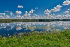 Lac reflétant les cieux bleus avec des nuages Images libres de droits