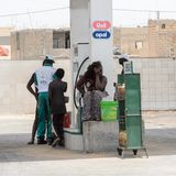 Unidentified Senegalese man fills the jerrycans up with gas. stock photos