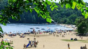 Lac-Simon, Quebec, Canada – July 29, 2018: People enjoy a sunny day on the beach of lake. Going to a beach of Lac-Simon for a s. Wim is a typical leisure royalty free stock photos