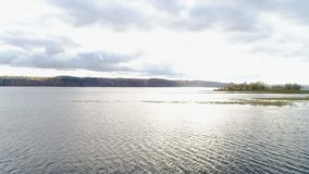 Lac tranquille bird eye view avec de petites îles et ciel nuageux banque de vidéos