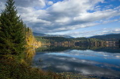 Lac tranquille de montagne reflétant le ciel nuageux Image libre de droits