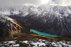 Lac turquoise parmi les montagnes couronnées de neige Image stock